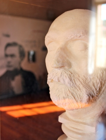 Plaster death mask of Alfred Nobel with a photograph of his younger self in the background